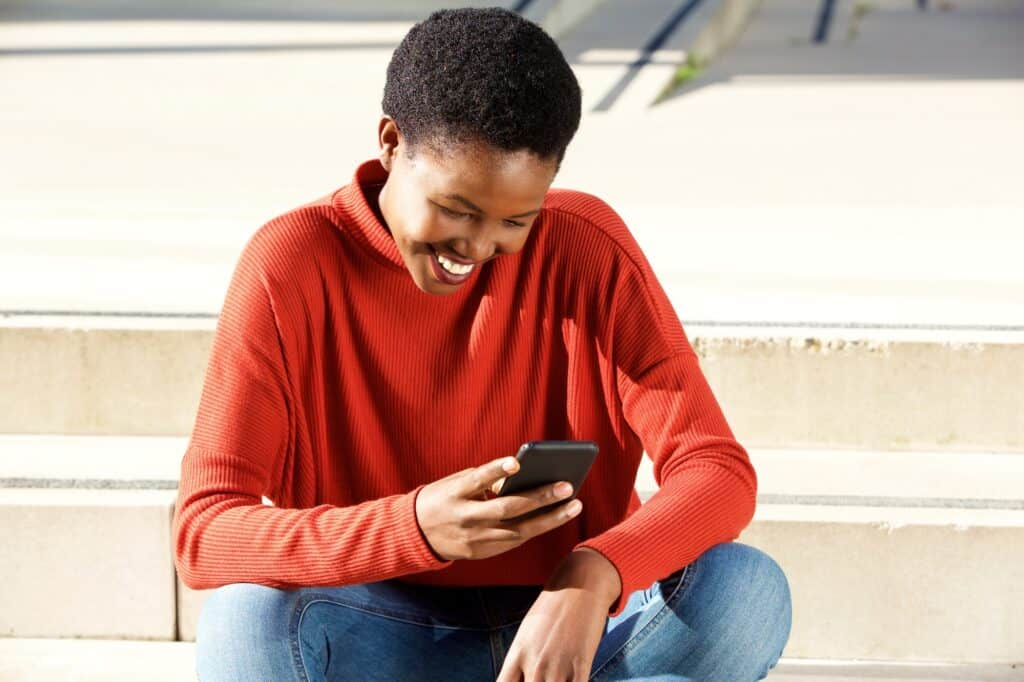 smiling young black woman looking at cellphone outdoors