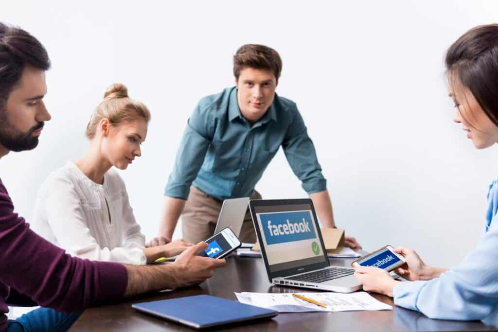 Young businesspeople using digital devices with facebook logo icons on screens