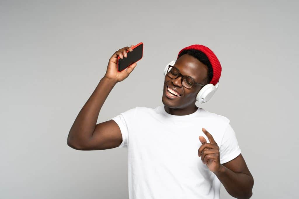 African American man with headphones enjoying listening to music, dances, holding mobile phone