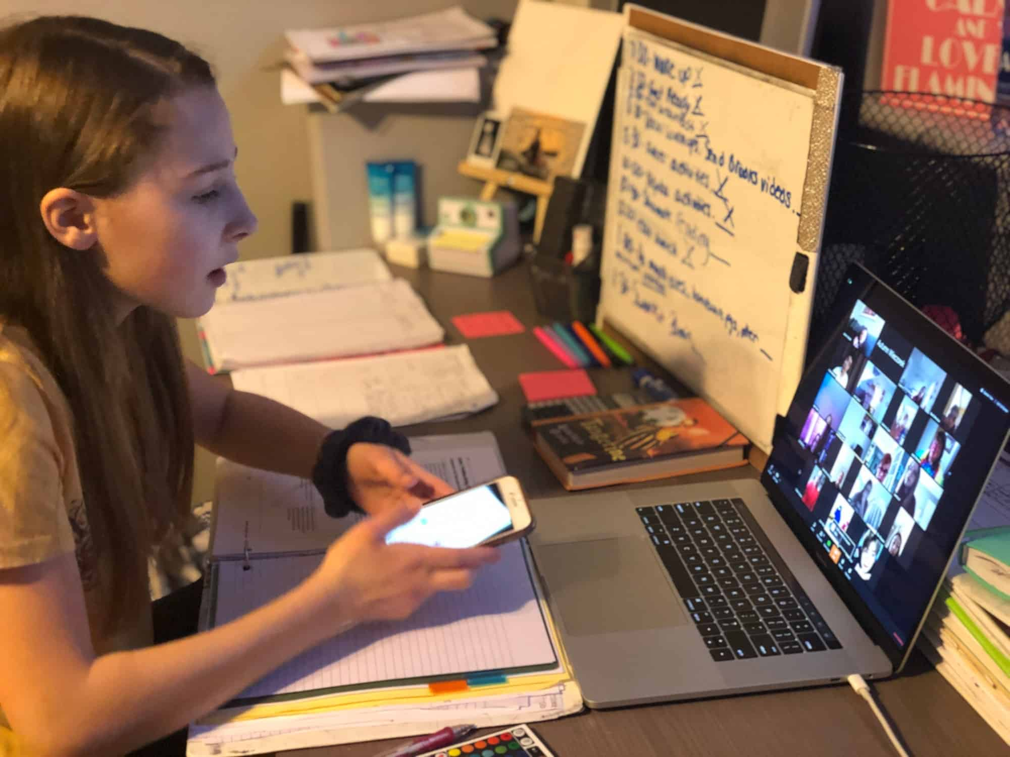 Teenage girl at home on a zoom call with her teacher and class.