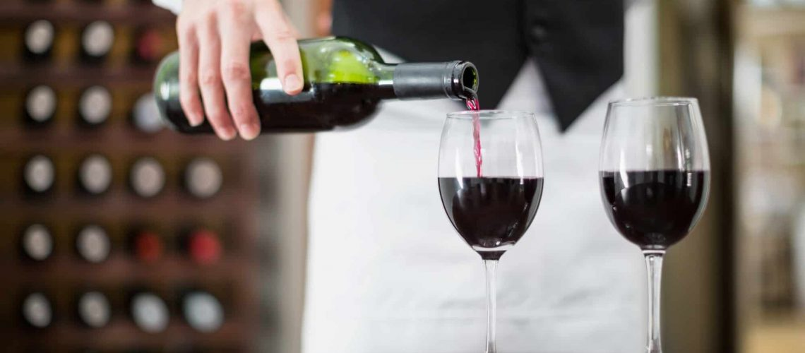 Male waiter pouring wine in wine glasses